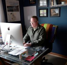 Image shows Mike Morris sitting and working at his computer desk with framed photos on the walls, in the background. Mike is wearing a green, botton down long-sleeved shirt and blue jeans.
