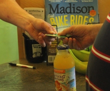 Image shows, to the left, the hand of a restaurant cashier grabbing a credit card from another hand of a blind patron, directly to the right. In the background, a bottle of orange juice rests on a brown counter top. Also in the background of the credit card exchange, to the right, is a rack filled with magazines, and a stack of menus resting between a black cup and a raised portion of the counter. The image of the credit card being exchanged between two hands evokes the types of customer service interactions between sighted and unsighted people that Chad writes about in this post.