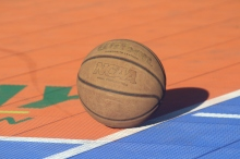 Image shows a basketball lying on a court during a bright, sunny day. The basketball is orange and slightly worn. It is resting at the right corner of the free-throw line, which is painted white. Part of the court is bright orange, but a strip of blue is featured to the right and directly in front of the ball. The ball casts a shadow onto the court.