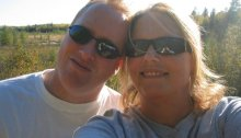 Mike Morris, left, poses for a selfie with his wife, Renee. Mike is wearing a white T-shirt and sunglasses, while Renee is wearing a gray shirt and sunglasses. Both are smiling. In the background is a hillside with trees, brush and a small body of water. It's a bright, sunny day.