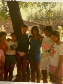 Image shows a group of six campers huddled together, with their arms around each other's shoulders. In this photo from the 1980s, the campers are smiling and enjoying a warm, sunny day at the Lions Camp in Rosholt, Wisconsin. The group, wearing T-shirts, shorts and swim wear, is huddled underneath a tall tree. In the background is a large building with a handicap accessible entrance. A wooded area lies just to the right of the building.