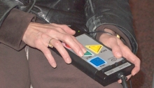 Image shows a tightly-cropped photo of a woman's hands holding a remote control used for a voting machine. The remote control has blue, yellow, green and red buttons across its surface. In her right hand, the woman is running two fingers across the green button, while the left hand is holding the top of the remote. Only her hands, the remote and part of her waist can been seen.
