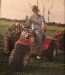 This image from the late 1980s shows Chad Nelson, age 16, sitting on a three-wheeled, all-terrain vehicle on a warm, sunny day. Chad, wearing a blue T-shirt and jeans, with a red baseball cap, is smiling and has both hands on the handlebars. In the background is two flower beds and a large field with a tree line off in the distance.