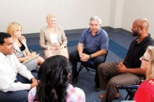 Image shows a support group of seven people, sitting in a circle, close to each other. The members are of varying ages and ethnicities. Most of the members are smiling as the group looks engaged in conversation.