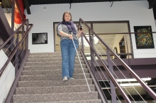 Ericka Short is shown confidently walking down the steps at the Council office. Ericka, wearing a purple scarf, striped shirt and blue jeans, has her sunglasses in her left hand and her white cane in her right, leading her down the gray stairway.