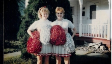 Image shows Janell Groskreutz at 16, standing next to a friend. Both are dressed in white high school cheerleader uniforms with a white skirt with red trim. Janell, on the left, is holding red and white pom poms and has a red bow in her hair. Both girls are smiling in this posed photo.
