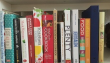 The image shows a row of colorful cookbooks displayed on a white bookshelf at Annika Konrad's home. The cookbooks encompass a wide-range of cooking styles, tastes and genres, from Swedish cake-baking to Mediterranean cuisine and it also features classic recipes from Julia Child to innovative cooking techniques from Jamie Oliver. The variety of cookbooks highlight Annika's joy in discovering new recipes from around the world, along with creative and accessible ways to cook.