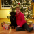 Image shows Janell Groskreutz, right, with her guide dog, Sully, a black lab. Janell and Sully are sitting close to each other on the floor and Janell has a bright, beautiful smile on her face. She is pleased to be finished with holiday shopping, eagerly anticipating Christmas Eve when her family opens their presents and she hears excitement and happiness in their reactions. A lighted, fully-decorated Christmas tree sparkles in the background and presents are spread along the hardwood floor, surrounding Sully and Janell.