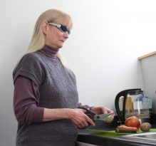 Image shows Judith Rasmussen using a pair of heavy-duty scissors to chop a stalk of celery. Judith is steadily holding the celery in her left hand and the scissors in her right hand and is focused on cutting the vegetable. On a countertop, just in front of Judith, lies an apple, potato, carrot and paring knife, resting atop a cutting sheet. Sunshine peers in through a window, illuminating the kitchen as Judith intently chops the celery.
