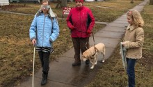 "Katherine Schneider is joined by two of her ""Blindness 101"" students on a walk through a neighborhood of houses on a cool spring day. As they walk down the sidewalk, one young lady is blindfolded and using a white cane. Not far behind her is Kathie, her guide dog besides her. The second student, with her blindfold removed and held in her hand, observes from the grass adjacent to the sidewalk."