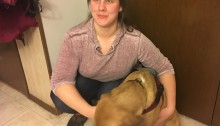 Meghan Whalen crouches down to wrap her arms around her guide dog, Amiera. She rests her right elbow on her right knee while she embraces Amiera with her left. Meghan smiles forward as Amiera's face points towards the floor.