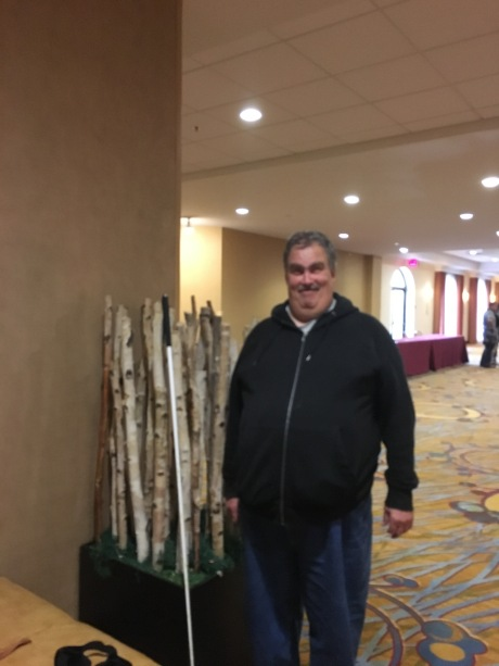 Image Description: Chad Nelson, wearing a black jacket and dark-colored pants, stands, facing the camera and smiling. His cane is to the left and in front of an artful display of birch branches standing on the vertical. Behind Chad is a lighted and windowed room in a conference center.