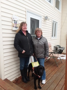 Janell, wearing a dark-toned coat stands to the left of her mother, who is wearing a lighter-toned winter coat. Janell holds Sully's harness. Sully, a black lab, stands in front of the women and is looking toward the camera. All are standing on a snowy wooden front porch.